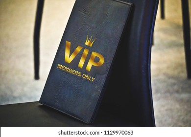 Invitation card on the chair in restaurant, hotel or cafe. Gold letter.  Guest Book Invitation, label VIP club party premium.important person