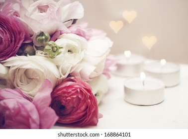 Invitation card. Ranunculus with candles and romantic light