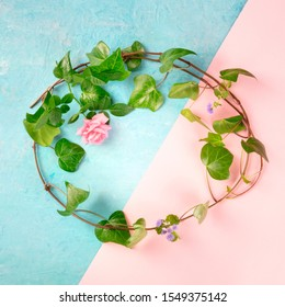 Invitation or greeting card square design template with a flatlay wreath of leaves and flowers, shot from above on a blue and pink background with copy space. Ivy and rose frame