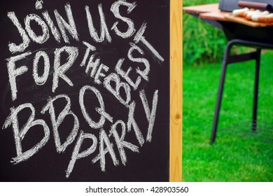 An Invitation To A Summer Barbecue Grill Party, Written on Blackboard, Barbecue Charcoal Grill Appliance And Outdoor Wooden Furniture On The Backyard Lawn In The Background