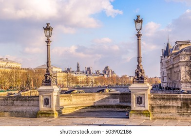 An inviting Bastide of the Pont Neuf between Rive-droite and the Cite, the Prefecture and the Hotel de Ville in the background, with traditional lampposts. A sunny winter afternoon in Paris, France