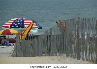 An inviting beach scene complete with sand, ocean, umbrellas and a rickety beach fence.