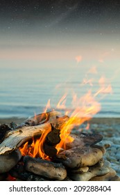 Inviting campfire on the beach during the summer. Elements of this image furnished by NASA