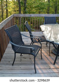 An inviting chair pulled out from the table on a deck in the woods