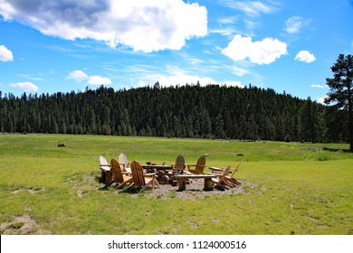 Inviting circle of chairs around a firepit reminding you of a summer camp.
