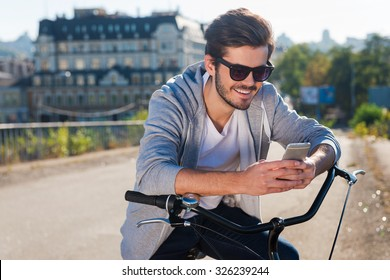 Inviting friend for a ride. Handsome young smiling man leaning at his bicycle and looking at his mobile phone while standing outdoors