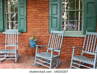 Inviting front porch with brick wall and floor, warm green shutters and trio of rocking chairs for company to sit and relax on ,