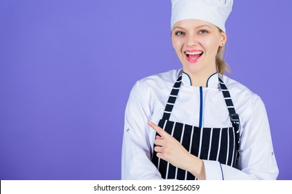 Inviting to her master class in culinary school. Happy master cook. Professional cook smiling and pointing away. Master chef wearing cook uniform and white hat. Master of her craft, copy space.