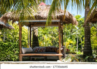 An inviting outdoor daybed sits vacantly among surrounding palm trees