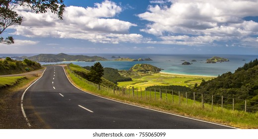 Inviting road through New Zealand countryside with blue sea with tropical islands at Bay of Islands, Northland, New Zealand