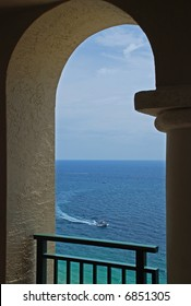 An inviting view of a boat on the ocean through an arch of a balcony.