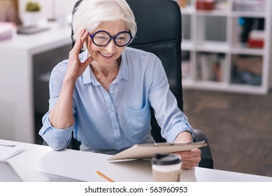 Involved charming aged woman working in the office
