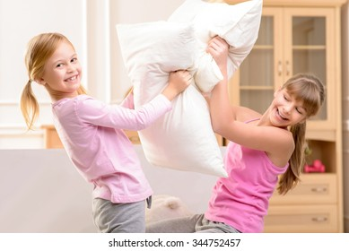 Involved in game. Pleasant nice little sisters holding pillows and fighting with them while feeling happy