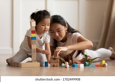 Involved little daughter her vietnamese mother play on warm floor using wooden colorful blocks create towers and buildings improve fine motor skill of kid. Funny educational games for children concept