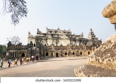 Inwa, Myanmar - April 2019: Buddhist pilgrims walking next to Me Nu Brick Monastery in Mandalay region.