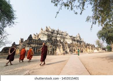 Inwa, Myanmar - April 2019: Buddhist monks walking next to Me Nu Brick Monastery in Mandalay region.