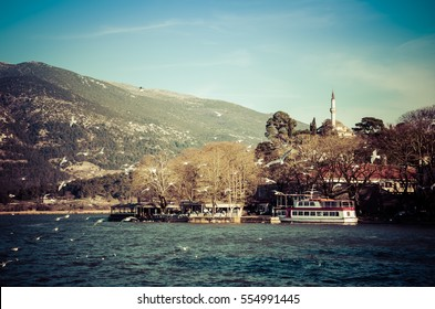 Ioannina city in Greece. View of the lake and the mosque of Aslan Pasa cami with flying sea gulls.