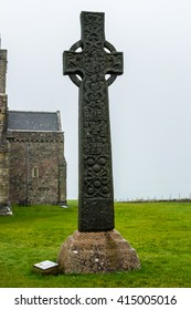 IONA, ARGYLL, SCOTLAND - SEPTEMBER 25, 2014: celtic high cross at medieval Iona Abbey, near Mull, in the Inner Hebrides. The flourish carved stone salutes tourists, pilgrims to the christian monastery