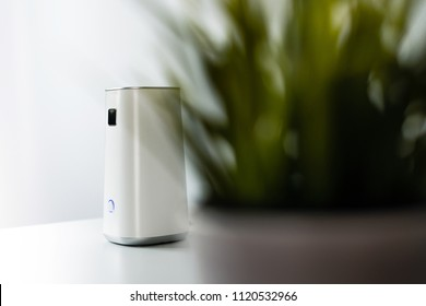 Ionizer stands on a white shelf on a white background. Air purifier at work, taking care of the comfort of residents, employees in the office. Getting rid of dust, smog, viruses, fungi from the air.