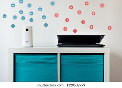 Ionizer stands on a white shelf on a white background. Air purifier during operation. A ionizer that releases negative ions and a laptop that releases positive ions. Caring for clean air at home.