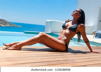 Ios, Greece, 06-13-2016, beautiful woman relaxing beside the water pool in the hotel