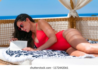 Ios, Greece, 06-13-2016, woman is reading a book at her vacation