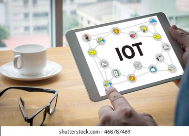 IOT business man hand working and internet of things (IoT) word diagram as concept