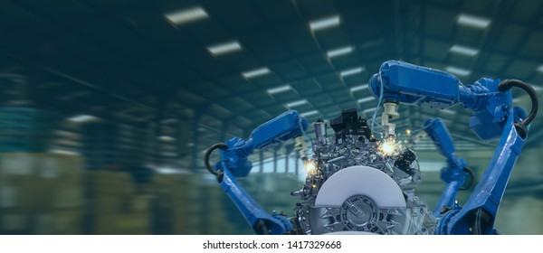 iot industry 4.0 technology concept.Smart factory using trending automation robotic arms with part on conveyor belt in operation line. Automotive manufacturing use it for precision, Repetition, intens