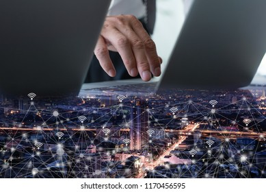 IoT, Internet of Things. Double exposure of business man working on laptop computer and night city view and internet network, wireless communication technology, smart city concept