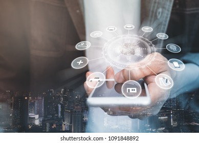 IoT, Internet of Things and smart city. Man using mobile smartphone with  sign and icon graphics interface on screen. Digital banking or omni channel concept. Wireless network connection