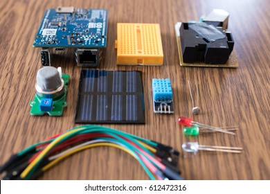 IoT kit components for educational science experiment. Microcontroller, dust sensor, gas sensor, solar panel, wires, led, humidity sensor and breadboard. DIY weather station for cloud