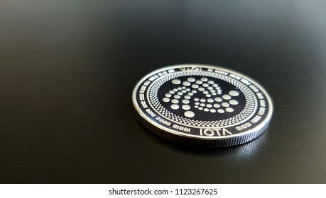 IOTA cryptocurrency coin laying on a dark themed background. The (MIOTA) coin is clear and in focus.