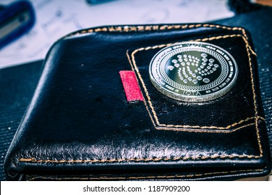 The iota cryptocurrency coin on leather wallet.