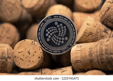 Iota cryptocurrency physical coin placed in between wine cork pile