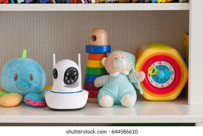 IP camera on the shelf with toys, serving as a baby monitor