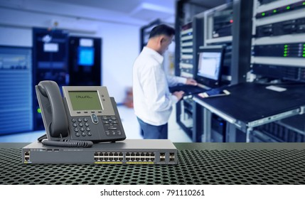 IP Telephone and Network switch 24 port gigabit and blur network administrator in data center room