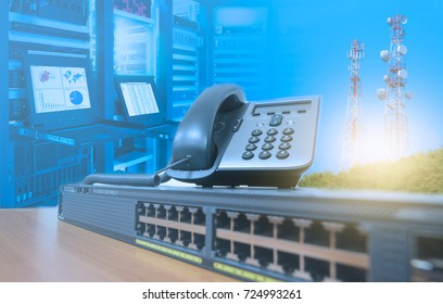 IP telephone on networking switch with blurred server rack cabinet data center room and telecommunication tower