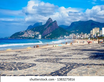 Ipanema beach with mosaic of sidewalk and mountain Dois Irmao (Two Brother)  in Rio de Janeiro, Brazil. Ipanema beach is the most famous beach of Rio de Janeiro, Brazil. Cityscape of Rio de Janeiro