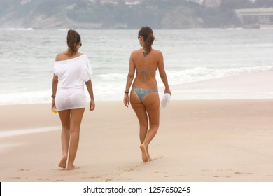 IPANEMA BEACH, RIO DE JANEIRO, BRAZIL - APRIL 6, 2011: Two young and attractive woman walking for the beach at the afternoon. One girl in bikini, the other dressed. Friends enjoying the beach.