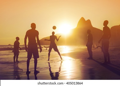 Ipanema beach, Rio de Janeiro, Brazil, silhouette of locals playing football at sunset.