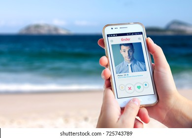 IPANEMA BEACH, RIO DE JANEIRO, BRAZIL - MARCH 15, 2016: Woman on the beach with a cell phone in her hands. On the screen you can see the Tinder application with a man profile open.