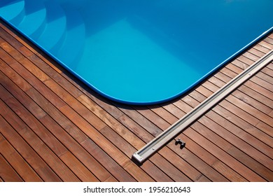 Ipe wood deck and swimming pool. Backyard poolside decking design, blue water contrasting with tropical hardwood boards, and beautiful wooden structure.