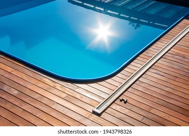Ipe wood decking around the pool, edge of the outdoor swimming pool with sun reflection on the blue water, tropical hardwood deck close up