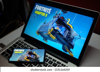 Iphone 11 pro and macbook with the fortnite 2 logo. Fortnite is a video game developed by the company Epic Games. United States, New York, Monday, October 14, 2019