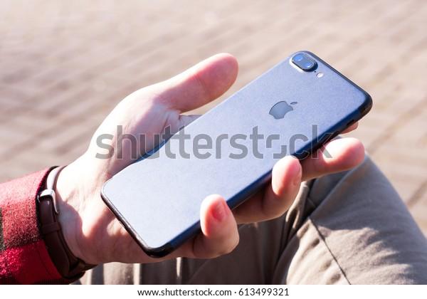iPhone 7 plus jet black with blue matt skin in man's hand.  Minsk, Belarus. April 2, 2017.