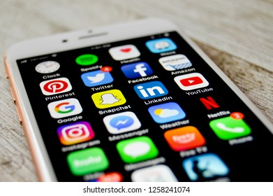 iPhone with assorted social media apps on a wooden surface