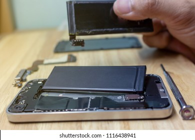 Iphone repairs install battery into the motherboard for smartphone By technician on desk
