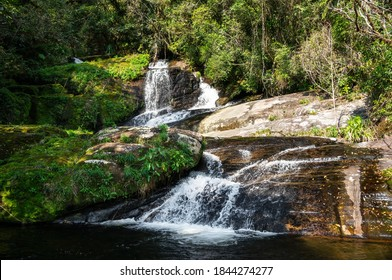 Ipiranguinha waterfall with his water current flowing around rock formations and creating a golden natural pool right below in the dense Serra do Mar (Sea Ridge) forest in Cunha, Sao Paulo - Brazil.