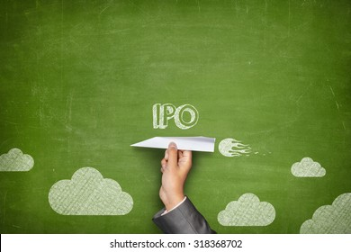 IPO concept on green blackboard with businessman hand holding paper plane