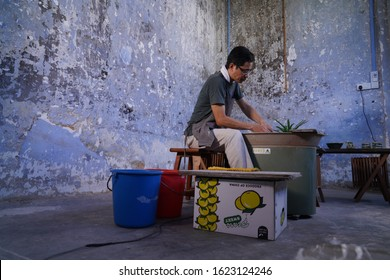 IPOH, MALAYSIA - JANUARY 22ND, 2019. Asian male sculpts new earthenware with tools and water. Man's fingers work with clay on the potter wheel.